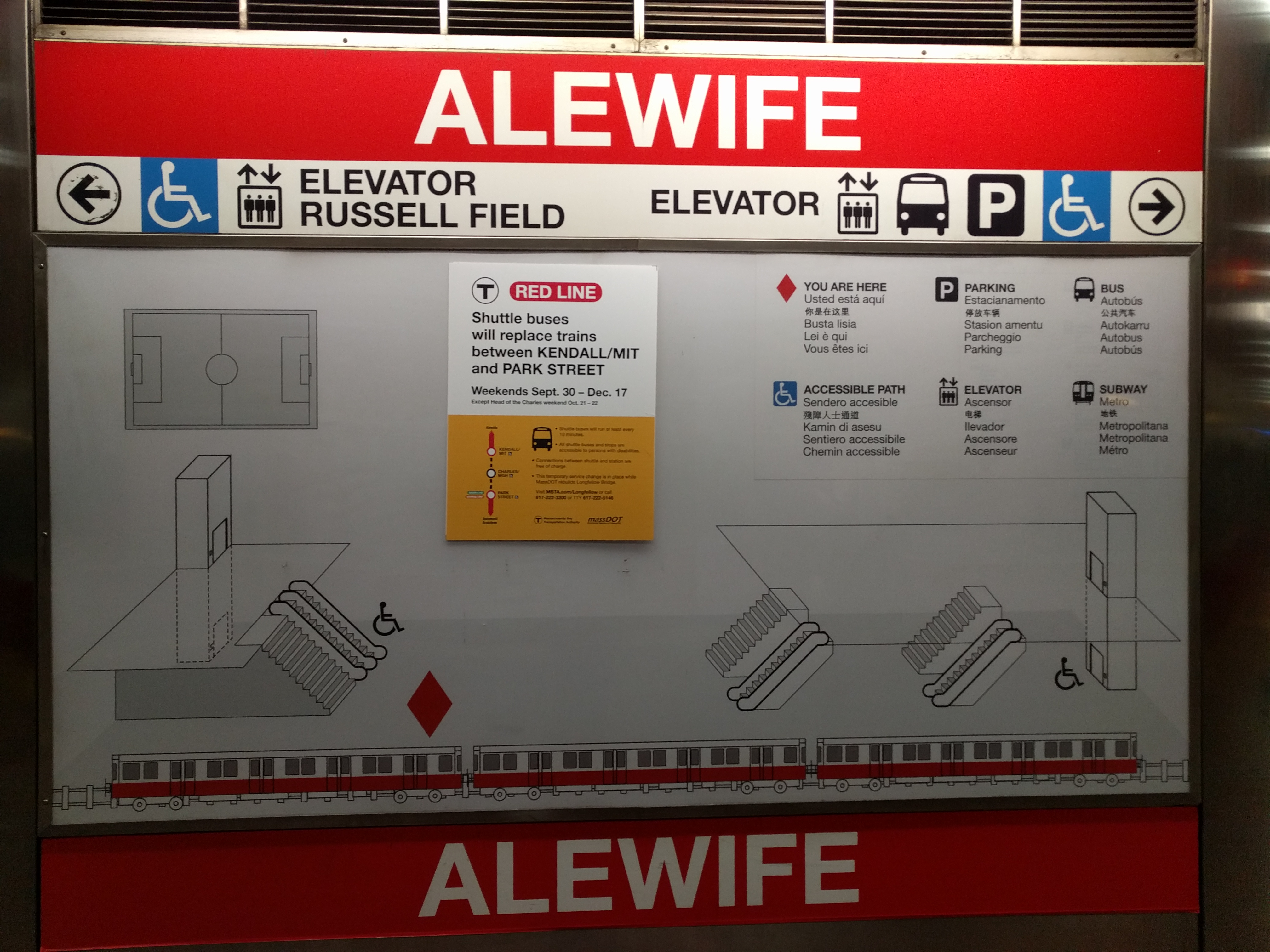 A photo of a map on the Alewife platform. It has an almost cartoonish train and an almost isometric drawing of the layout of the stairs and escalators. There's a disruption notice stickered on top.