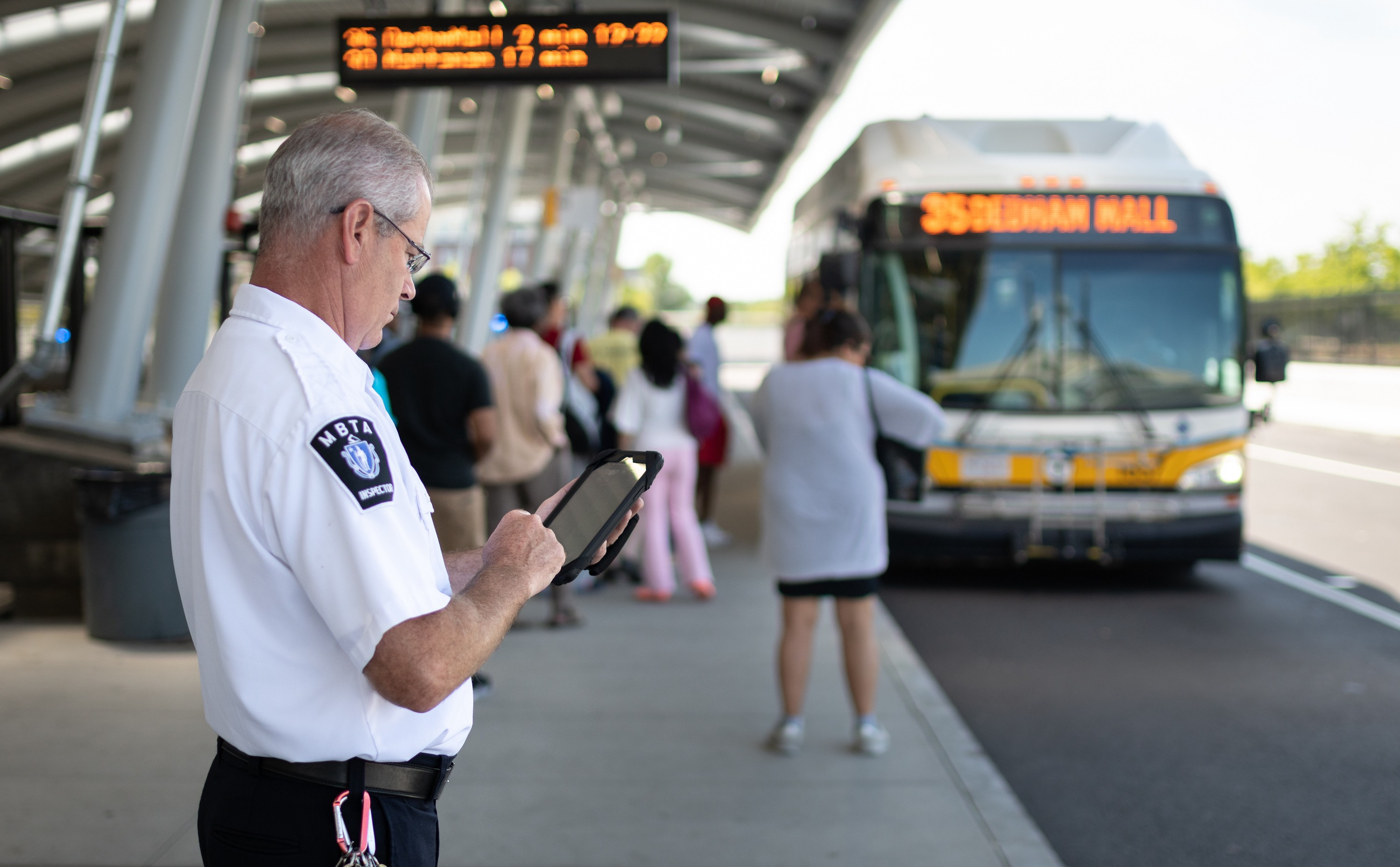 A bus inspector looks at a tablet on the Forest Hills bus platform.